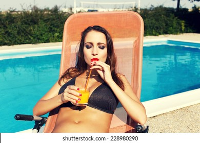 Woman drink orange juice with straw at swimming pool, summer holiday, vacation and relax