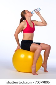 woman drink water after exercise sitting on pilates ball
