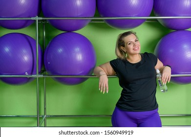 Woman drink water after intense training in a sports club. Fat blonde is resting in the gym between sets.