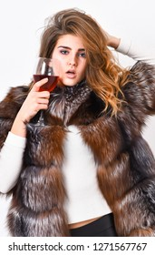 Woman drink wine. Girl fashion makeup wear fur coat hold glass alcohol. Elite leisure. Reasons drink red wine in wintertime. Lady fashion model curly hairstyle enjoy elite wine. Wine culture concept.