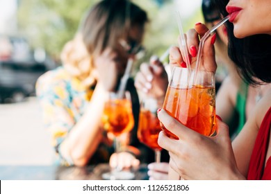 Woman drinking aperol spritz, with friends at dinner table