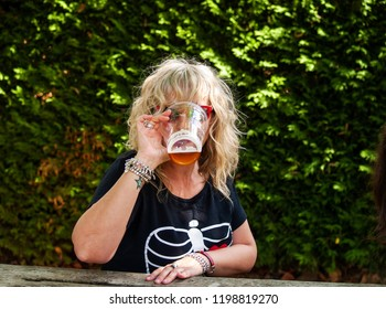 A woman drinking beer at an outdoor celebration