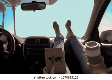 Woman drinking cappuccino inside car with feet on dashboard - Girl relaxing in auto trip reading book with palms clear sky in background - Traveler concept - Focus on feet - Image
