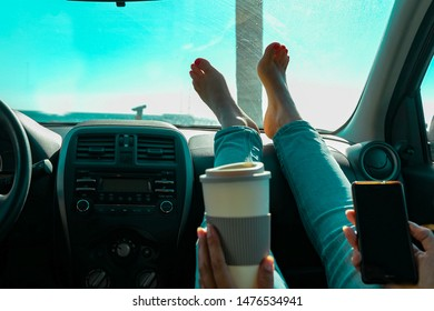 Woman drinking cappuccino inside car with feet on dashboard - Girl relaxing in auto looking cellular with palms clear sky in background  - Traveler concept - Focus on feet - Image