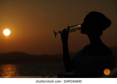 Woman drinking champange on yatch that sailing in the sea under the sun light.