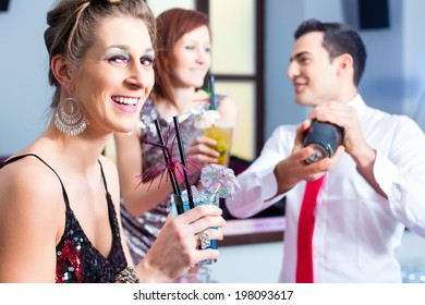 Woman drinking cocktails in fancy night club