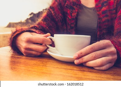 Woman drinking coffee by the sea