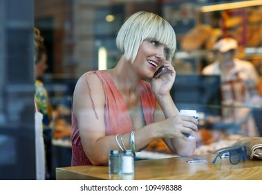 woman drinking coffee in the cafe window and talking to mobile phone
