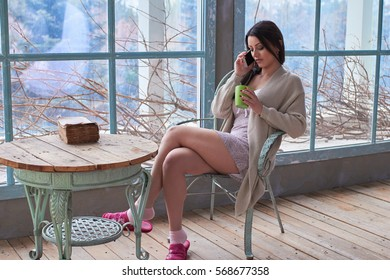 woman drinking coffee and calling with cellphone