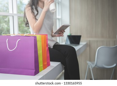 Woman is drinking a coffee from cup and holding the mobile phone with shopping bag for online shopping concept