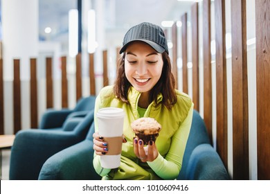 woman drinking coffee and eating a delicious muffin cake in modern cafe, fastfood and travel concept