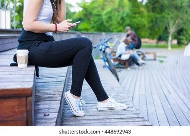 Woman drinking coffee. Girl listen music and relaxing after sports. Coffee to go concept. hipster student in the city park.