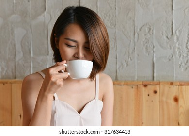 woman drinking coffee in the morning at restaurant (soft focus o