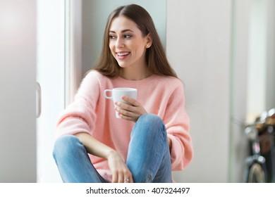 Woman drinking coffee near window