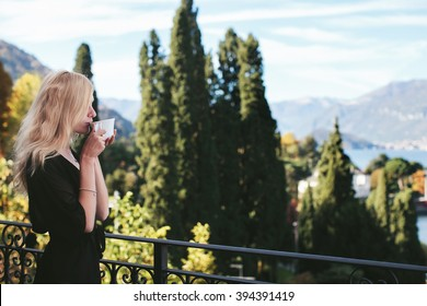 woman drinking coffee on the balcony in the morning overlooking the park at Lake Como