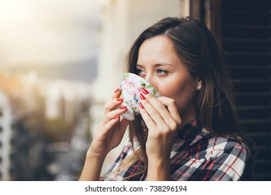 Woman is drinking coffee on a balcony. Close up of a woman holding in hands and drinking cup of coffee. Early morning routine
