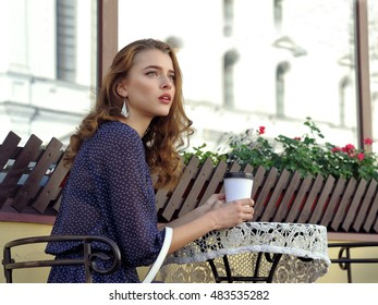 Woman drinking coffee in an outdoor cafe early morning