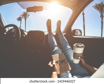 Woman drinking coffee paper cup inside car with feet on dashboard - Girl relaxing in auto trip reading traveler book with ocean beach and palms in background - Travel concept - Focus on hands