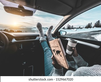 Woman drinking coffee paper cup inside car with feet warm socks on dashboard - Girl relaxing in auto trip reading travel book with snow mountains in background - Traveler concept - Focus on wood diary
