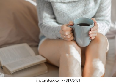 Woman drinking coffee and reading a book in bed