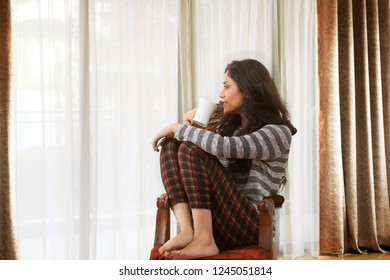 Woman drinking coffee and relaxing on armchair looking out from window