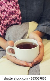 Woman drinking coffee sitting in bed