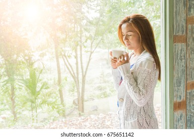 woman drinking coffee sitting by the window in the house.