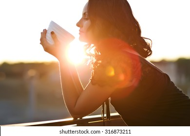 Woman drinking coffee in the sun, outdoor in sunlight light, enjoying her morning coffee.