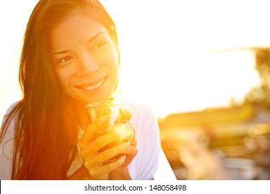 Woman drinking coffee in sunshine sitting outdoor in sun light enjoying her morning coffee. Smiling happy multiracial female Asian Chinese / Caucasian model in her 20s.