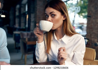 Woman drinking coffee at a table in a cafe