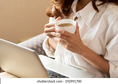 Woman drinking coffee and using digital tablet in the morning