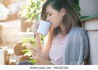 Woman drinking coffee, using smart phone and enjoying beautiful sunny day. Chilly morning, backlight