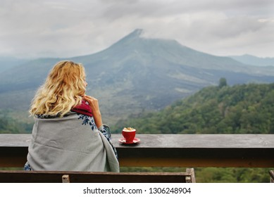 Woman drinking coffee with the view of Batur volcano in Kintamani, Bali, Indonesia