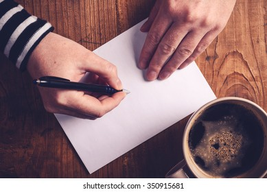 Woman drinking coffee and writing letters, top view of female hands writing recipient address on white envelope, retro toned image with selective focus.