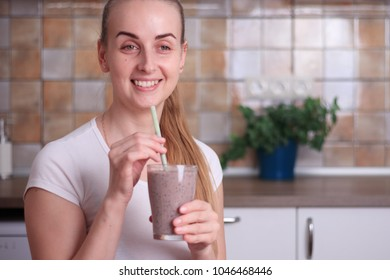 Woman is drinking fresh healthy blueberry smoothie