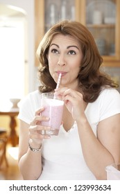 Woman drinking a fruit smoothie through a straw in kitchen setting looking up