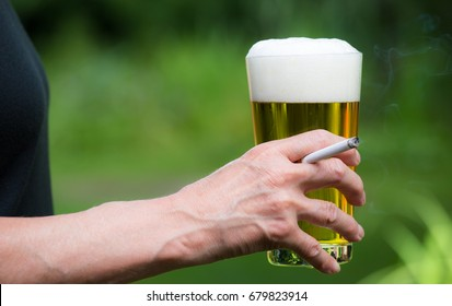 A woman drinking a glass of beer and smoking a cigarette
