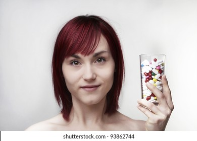 woman drinking a glass full of pills