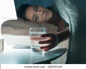 Woman drinking a glass of water before going to sleep, she is lying in bed