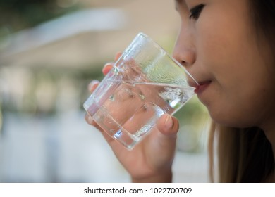 Woman drinking from a glass of water. Drink water for Healthy.