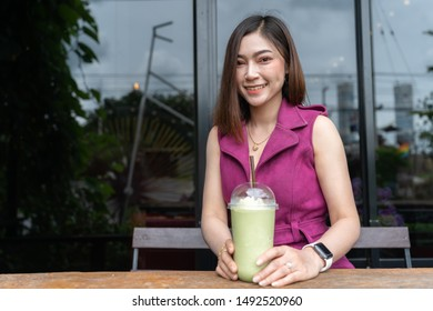 woman drinking green tea frappe in the cafe