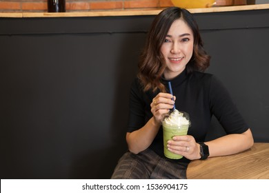 woman drinking green Tea frappe in a cafe