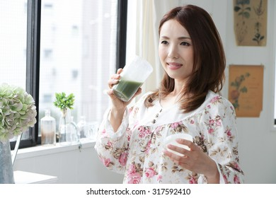woman drinking green vegetable smoothie