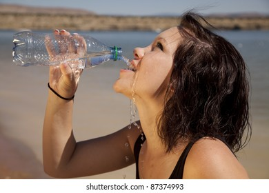 A woman drinking from her water bottle.
