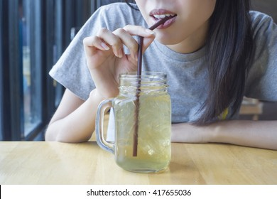 Woman drinking herbal drink from straw.