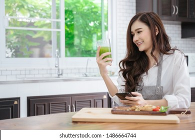 Woman drinking a homemade green detox juice, texting on her phone while sitting in her kitchen table