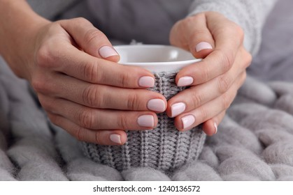 Woman drinking hot drink from cozy mug close up. Warmth concept