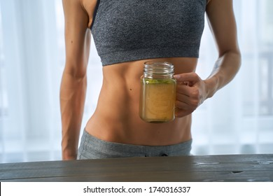 Woman drinking a hot drink. Sporty woman with a cup bone broth.