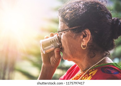 Woman drinking a hot tea in steel glass in her traditional house in himachal pardesh.