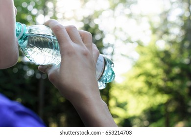 Woman drinking mineral water and resting while jogging in the park